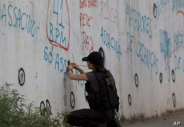 A police officer checks the bullet holes in the wall of the school where Maria Eduarda Conceicao was killed by a stray bullet during a shootout between police and alleged drug traffickers in the Acari neighborhood, in Rio de Janeiro, Brazil, April 12...
