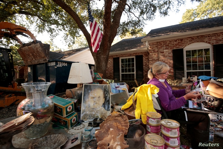 Ginger Benfield works to save family photos in the aftermath of tropical storm Harvey in west Houston, Texas, U.S. September 11, 2017.