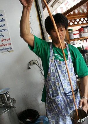 Suchart Lapaparat pours hot tea at his store inside the red shirt protest zone in central Bangkok. He says he is losing money from the protests.
