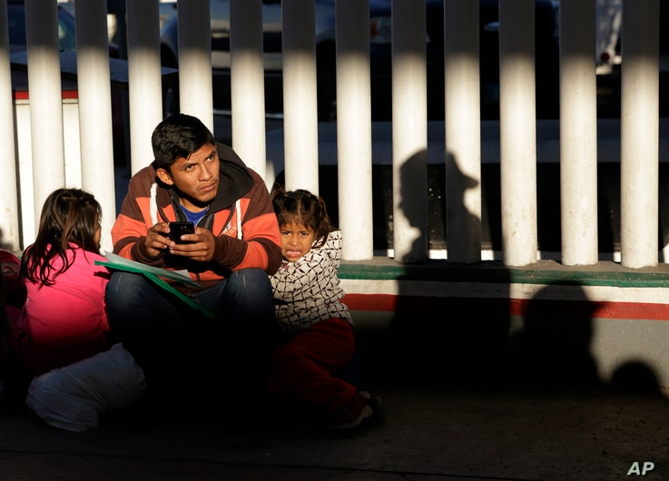 A migrant who did not give his name looks on with his children as they wait to hear if their number is called to apply for asylum in the United States, at the border Friday, Jan. 25, 2019, in Tijuana, Mexico.