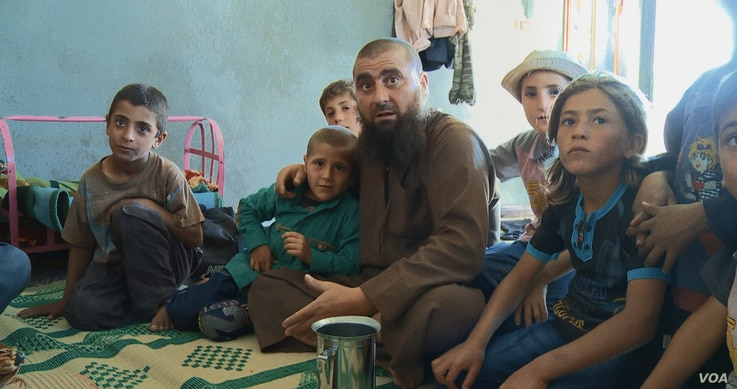 """Abu Osama, the main character in the documentary """"Of Fathers and Sons,"""" is surrounded by his children in his house in northern Syria. (Kahtan Hasson for VOA)"""