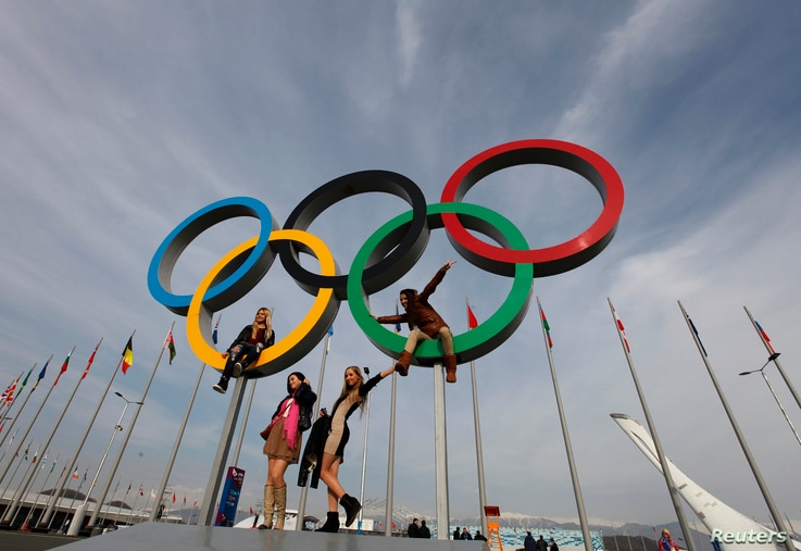 People pose for a picture with a set of Olympics rings at the Olympic Park a day after the closing ceremony for the 2014 Sochi Winter Olympics, Russia, Feb. 24, 2014.