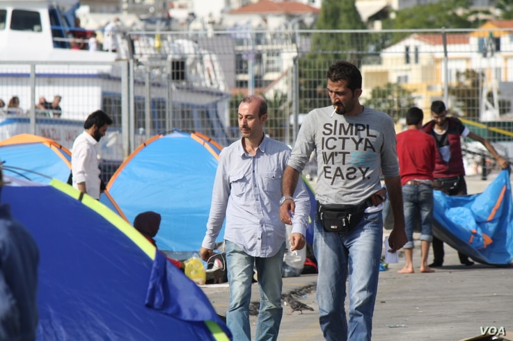 Refugees and other migrants arrive in Greek islands on dangerous boats before boarding a commercial ship to Athens.  Those without enough money for the ship areleft behind. (Heather Murdock/VOA)