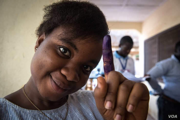 A woman shows off her inked finger after casting her ballot in Freetown, Sierra Leone, March 7, 2018. (Photo: Jason Patinkin / VOA)