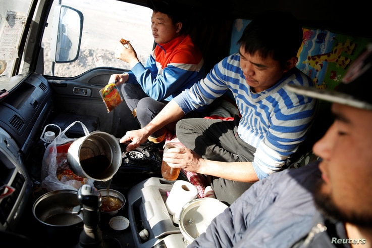 Three men eat a dinner of instant noodles and dried beef inside a truck at Khanbogd Soum, near the border with China, in the Gobi desert, Mongolia, Oct. 31, 2017. Truckers cook, eat and sleep in vehicles covered in coal dust, many subsisting on the s...