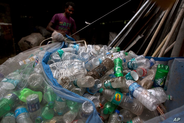 An Indian ragpicker man ties a net full of plastic bottles on the outskirts of Gauhati, India, June 5, 2017.