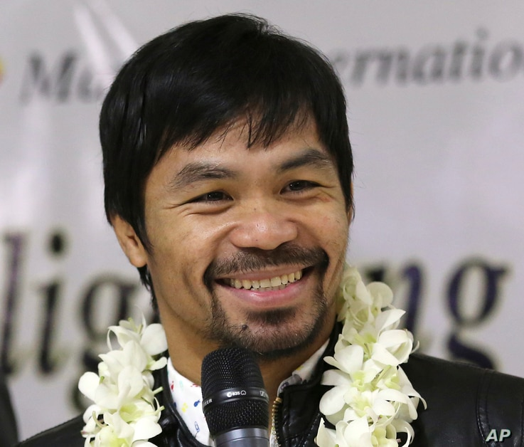 In this April 14, 2016 file photo - Filipino boxer and Congressman Manny Pacquiao smiles as he answers questions from reporters upon his arrival at the Ninoy Aquino International Airport in suburban Pasay city, south of Manila, Philippines, after bea...