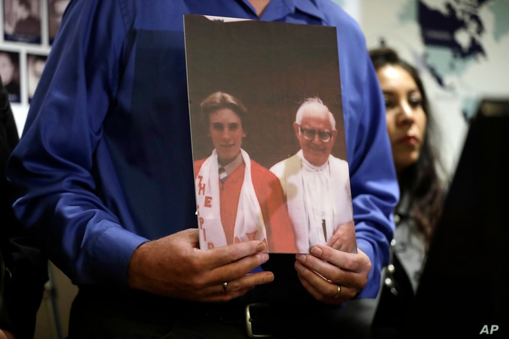 Tom Emens holds a picture of himself as a boy with, Monsignor Thomas Joseph Mohan, the priest who sexually abused him in the late 70s during a press conference Tuesday, Oct. 2, 2018, in Los Angeles.