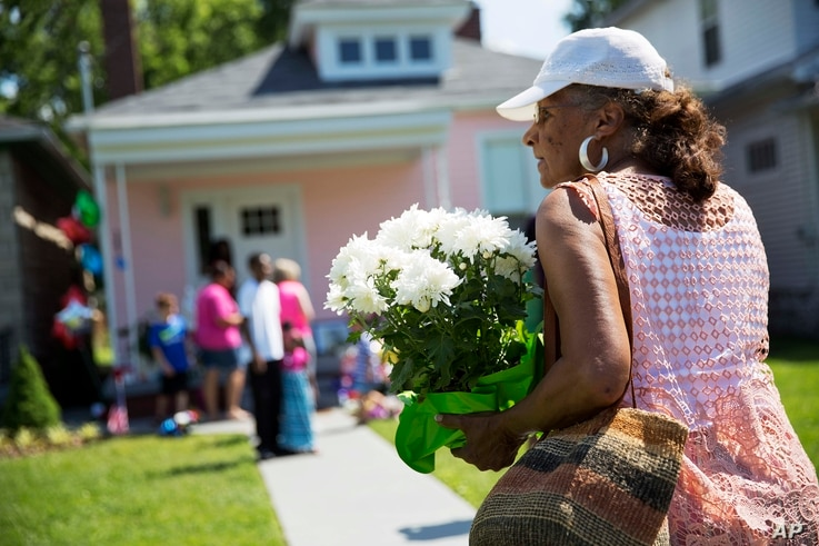 A mourner carries flowers to leave at the childhood home of Muhammad Ali, rear, June 5, 2016, in Louisville, Kentucky. The revered heavyweight champion who died Friday at the age of 74, is to be buried on June 10.