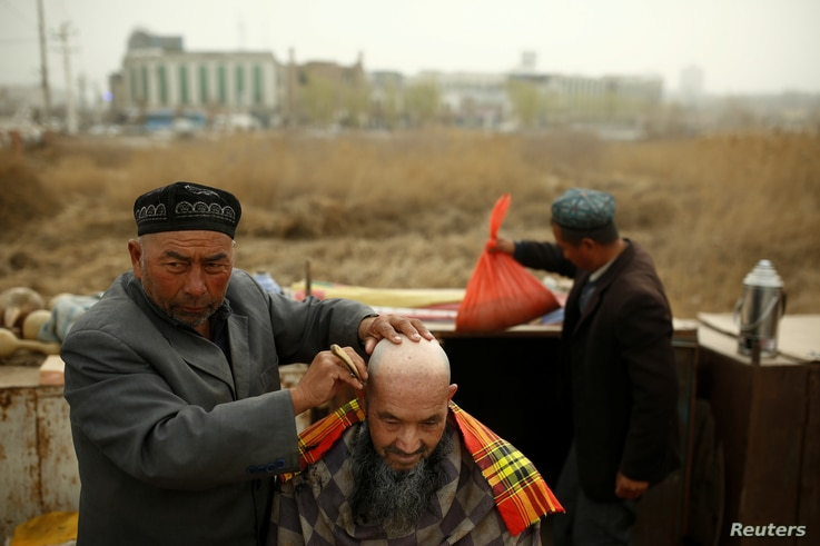 A street barber shaves the head of a man in Kashgar, Xinjiang Uighur Autonomous Region, China, March 24, 2017.