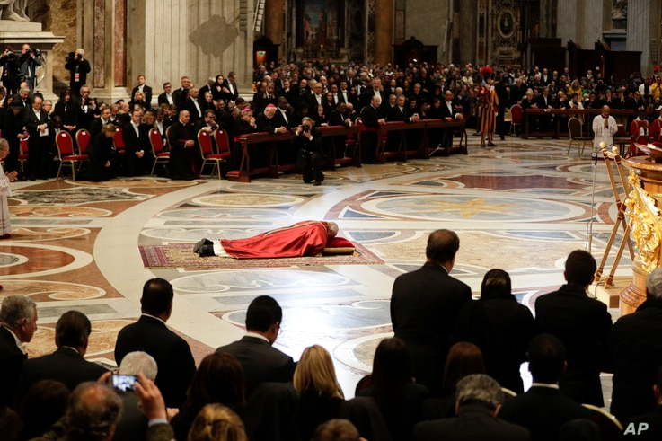Pope Francis prostrates himself in prayer during the Good Friday Passion of Christ Mass inside St. Peter's Basilica, at the Vatican, March 30, 2018.