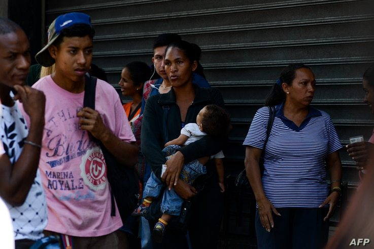 A woman holds her baby while queuing outside a supermarket in Caracas to buy basic food and household items, Nov. 10, 2017. In crisis-stricken Venezuela, the cost of the basic basket of goods soared to nearly 2.7 million bolivars in September, the eq...