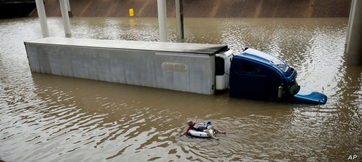 After helping the driver of the submerged truck get to safety, a man floats on the freeway flooded by Tropical Storm Harvey on Aug. 27, 2017, near downtown Houston.