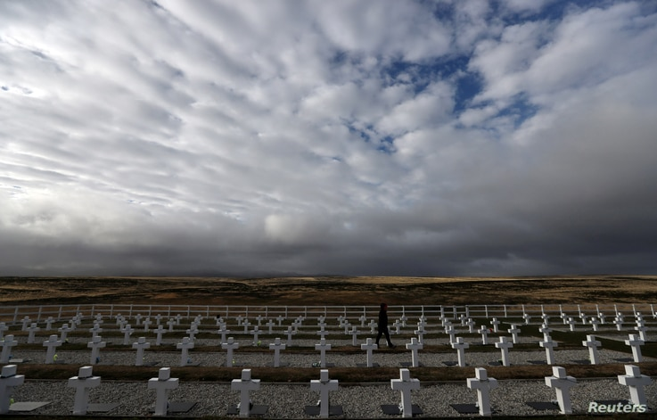 FILE - A woman visits Darwin cemetery, where Argentine soldiers who died during the Falklands war are buried, in the Falkland Islands, May 16, 2018.