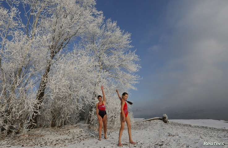 Nastya Usachyova, 9, and her mother Natalia, 39, members of the Cryophile winter swimmers club, warm up before swimming in the Yenisei River in the Siberian city of Krasnoyarsk, Russia, Nov. 14, 2015.