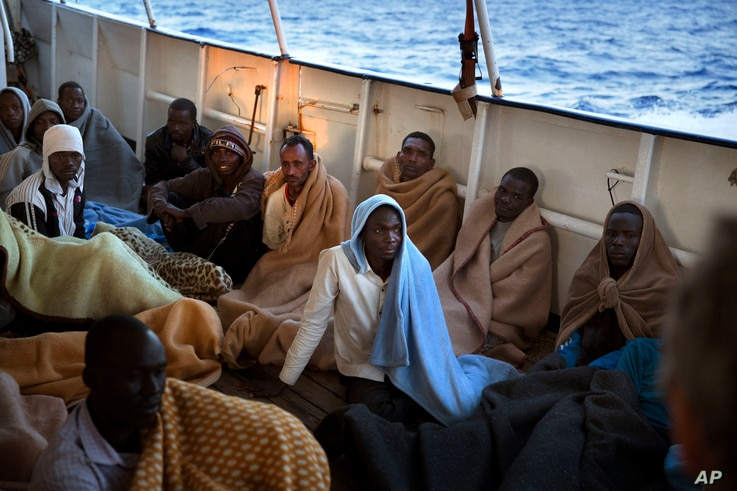 Men sit on the deck of the Golfo Azzurro rescue vessel after being rescued by members of the Spanish ONG Open Arms on the mediterranean sea, north of Zuwarah, Libya, June 21, 2017.