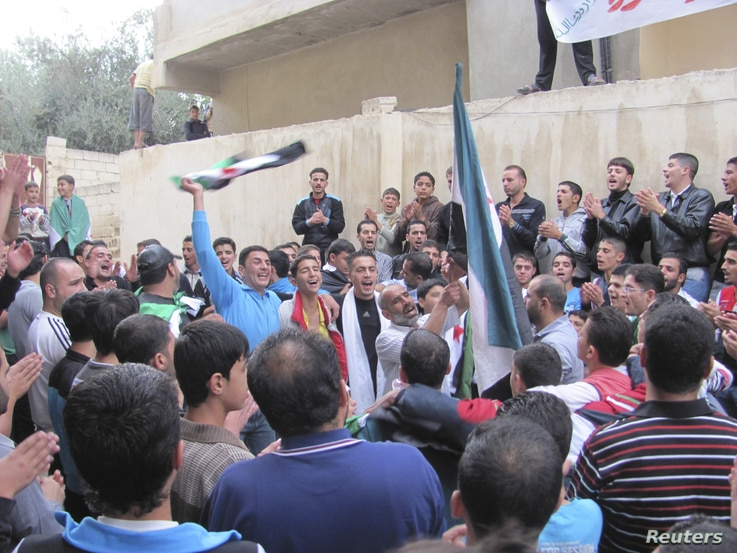 Demonstrators hold opposition flags during a protest against Syria's President Bashar al-Assad, after Eid al-Adha prayers, Dara, Syria, October 26, 2012.