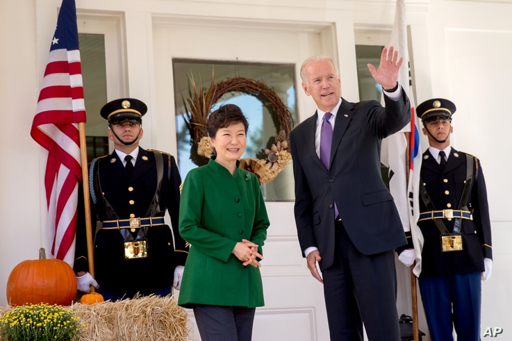 Vice President Joe Biden waves to reporters as South Korean President Park Geun-hye arrives for lunch at the Naval Observatory in Washington, Oct. 15, 2015.
