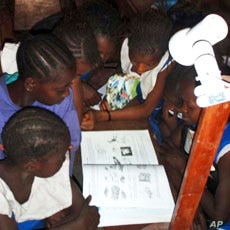 Girls in Sierra Leone read by the light of a single watt LED