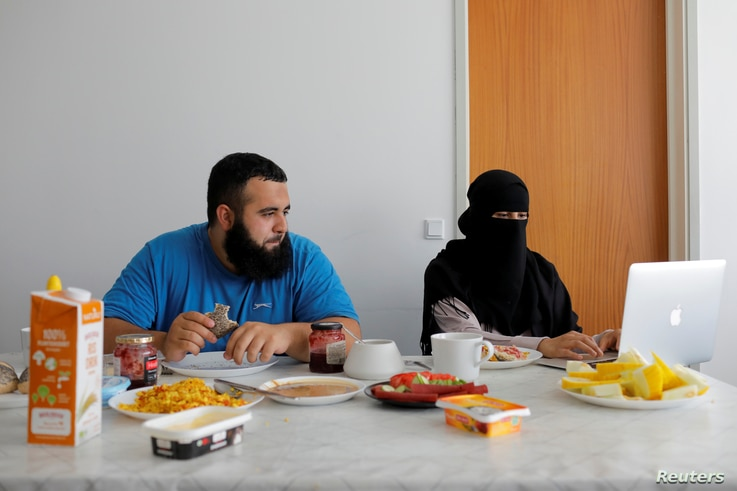 Meryem, 20, a wearer of the niqab and a member of the group Kvinder I Dialog (Women in Dialogue), sits with her husband Ali, 23, as she updates her blog Niqabi Nuancer over a vegan breakfast in Aarhus, Denmark, July 28, 2018.