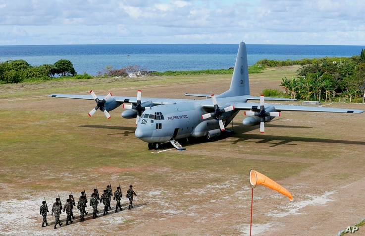 FILE - Philippine troops march as a Philippine Air Force C-130 transport plane carrying Philippine Defense Secretary Delfin Lorenzana, Armed Forces Chief Gen. Eduardo Ano and other officials, sits on the tarmac at the Philippine-claimed Thitu Island ...