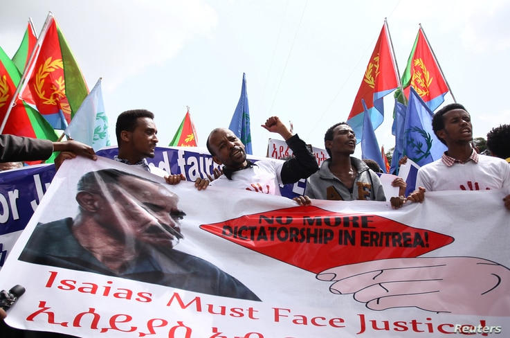 Eritrean refugees chant slogans as they hold a banner with the picture of President Isaias Afwerki during a demonstration in support of a U.N. human rights report accusing Eritrean leaders of crimes against humanity, in Ethiopia's capital, Addis Abab...