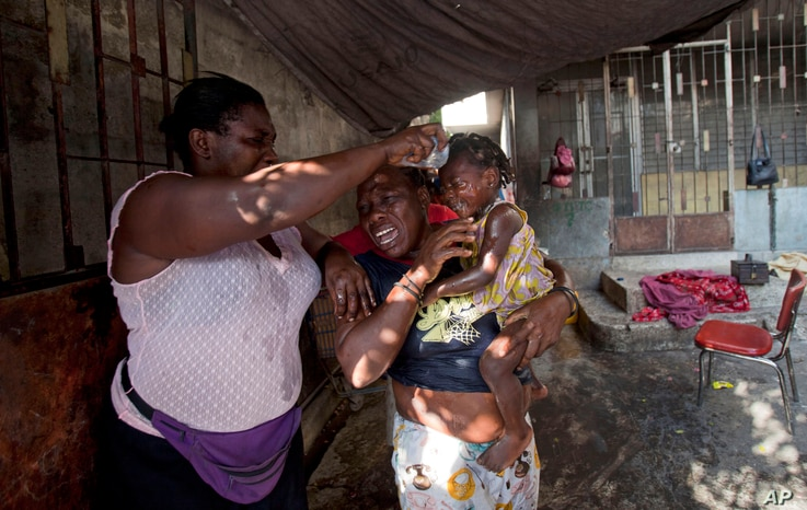 Residents douse a little girl's face with water after tear gas was fired by National Police near their home during clashes with anti-government protesters in Port-au-Prince, Haiti, Dec. 13, 2014.