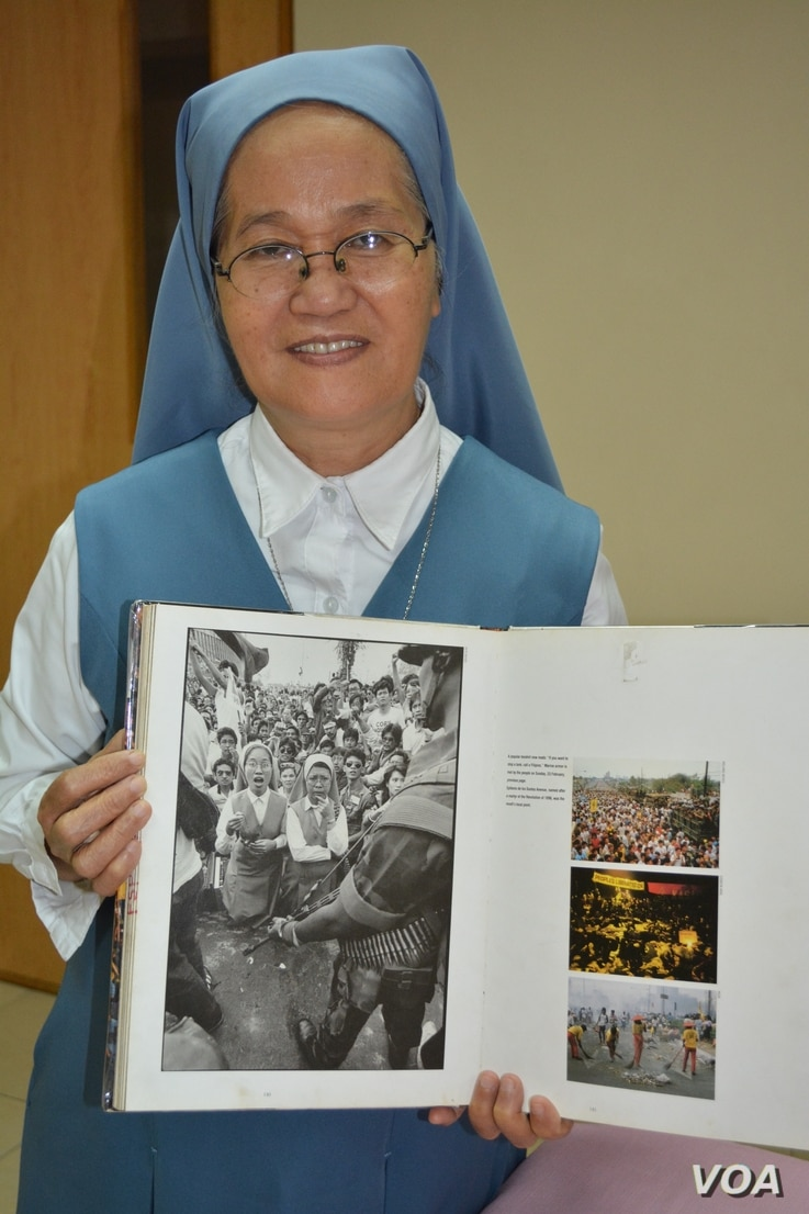 """Sister Porferia Ocariza holds a book with a photo of herself during the Philippines """"People Power Movement"""" that saw the ouster of dictator Ferdinand Marcos.  The photo by Pete Reyes of the Manila Times captures the stunned Ocariza as military tanks ..."""