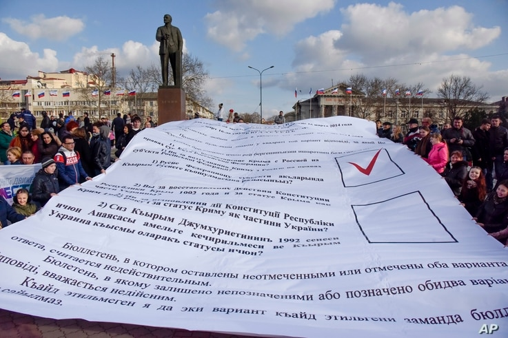 People hold a huge ballot used in a referendum on secession of Crimea from Ukraine as they gather to mark the third anniversary of the event in Simferopol, Crimea, March 18, 2017.