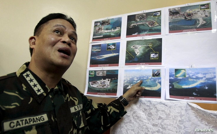 Armed Forces of the Philippines (AFP) Chief of Staff Gregorio Pio Catapang shows some images of the structures being built by China at the disputed islands during a news conference at the AFP headquarters in Manila, April 20, 2015.