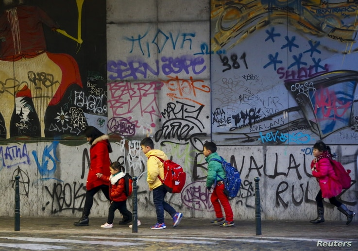 Children walk past graffiti on their way to school in central Brussels, Nov. 25, 2015.