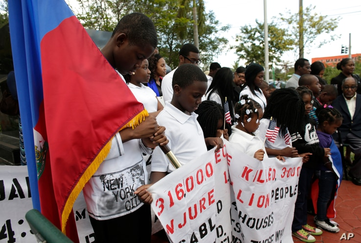 Widnay Charles, left, bows his head during a vigil to commemorate the seventh anniversary of the earthquake that devastated Haiti in 2010, Jan. 12, 2017, in the Little Haiti neighborhood of Miami.