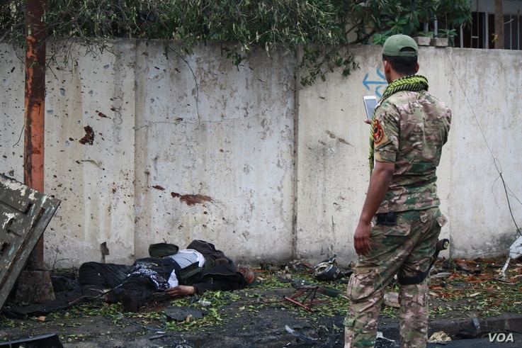 An Iraqi soldier takes pictures of a dead body in Mosul, March 2, 2017, that soldiers say belonged to an IS militant charged with sending armed drones to kill Iraqi forces in eastern Mosul. (H. Murdock/VOA)