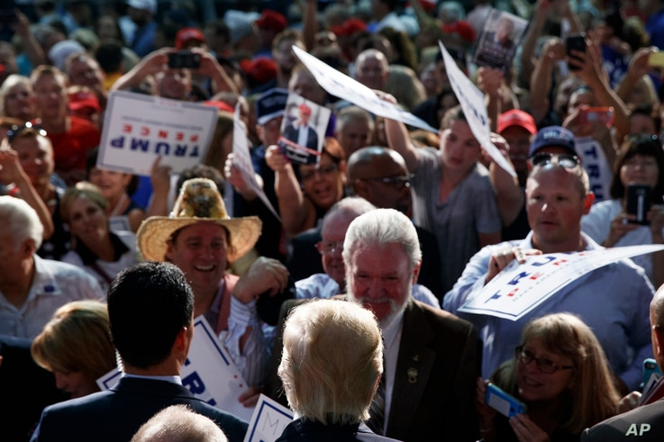 Republican presidential candidate Donald Trump shakes hands during a campaign rally at Wings Over the Rockies Air and Space Museum, Friday, July 29, 2016, in Denver.