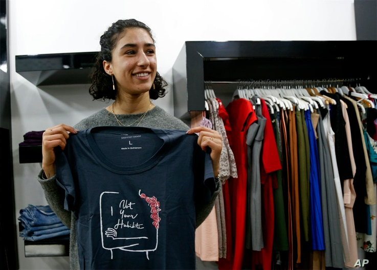 """Palestinian-American Yasmeen Mjalli holds one of her T-shirt designs with the slogan """"Not Your Habibti (darling)."""""""