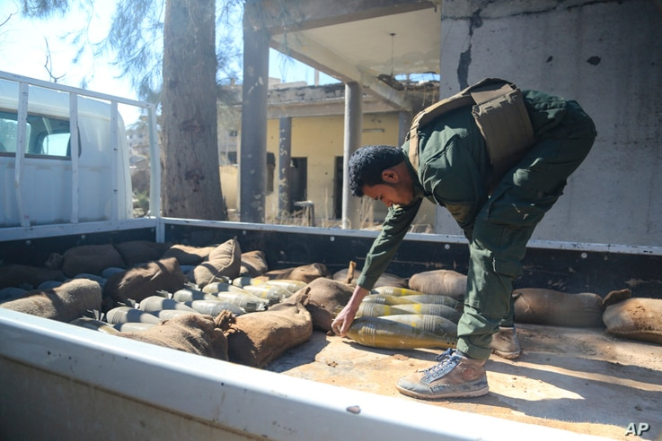 In this image provided by the U.S. Army, a Raqqah Internal Security Force member loads unexploded ordnance onto a truck for proper disposal in Raqqah, Syria, on Feb. 19, 2018.