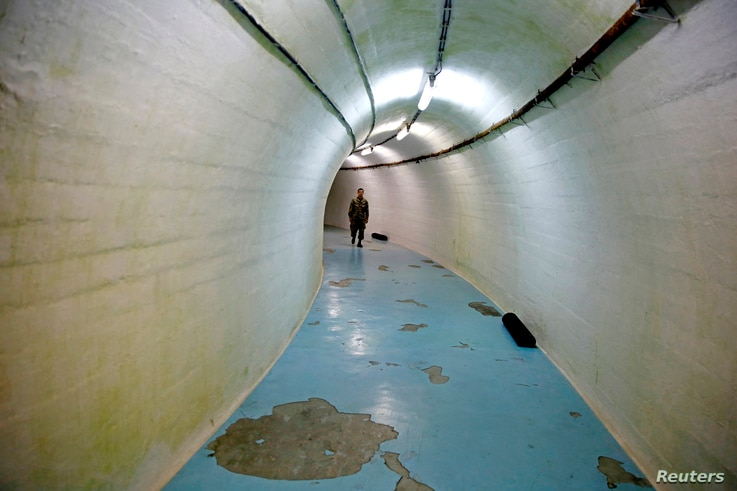 A member of the Armed Forces of Bosnia and Herzegovina walks through a tunnel in Josip Broz Tito's underground secret bunker (ARK) in Konjic, Oct. 16, 2014.