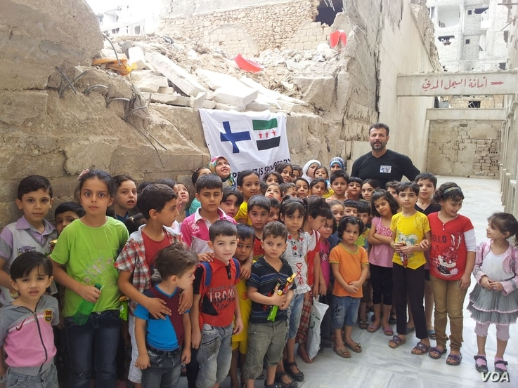 Rami Adham is surrounded by Syrian children who gather near a field school in Aleppo that has since been destroyed, Sept. 2015. (photo courtesy of Rami Adham)