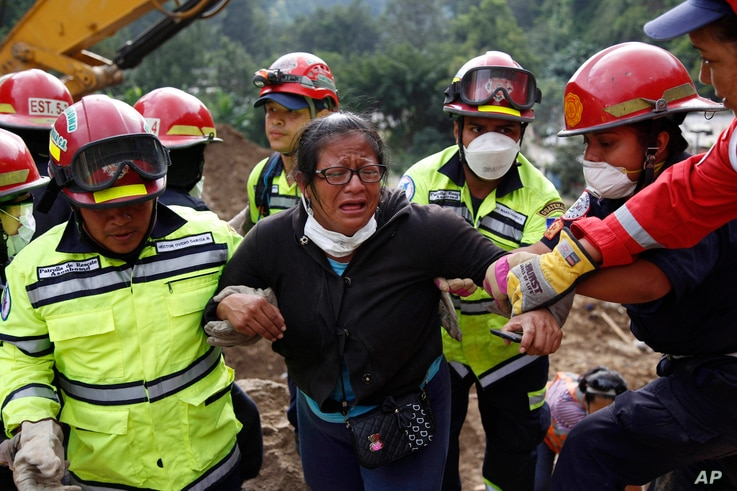 Rescue workers help a woman after she identified two family members as their bodies are retrieved from the site of a mudslide in Cambray, a neighborhood in the suburb of Santa Catarina Pinula, on the outskirts of Guatemala City, Oct. 3, 2015.