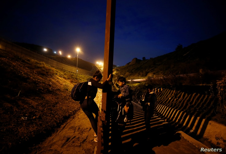 Migrants from Honduras, part of a caravan of thousands from Central America trying to reach the United States, jump the fence to cross it illegally into San Diego County, U.S. (L), taken from the border wall in Tijuana, Mexico (R) Jan. 16, 2019.