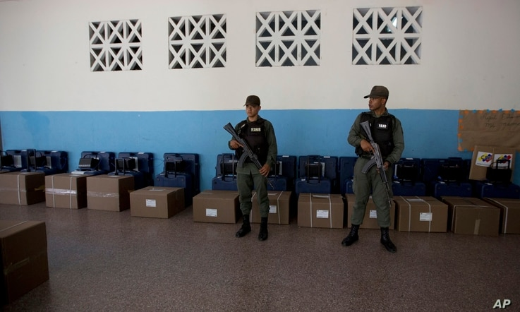 Venezuelan Bolivarian National Guard officers guard voting machines at a polling station, in Caracas, Venezuela, May 18, 2018. President Nicolas Maduro is seeking a new six-year mandate — and despite crippling hyperinflation and widespread shortage...