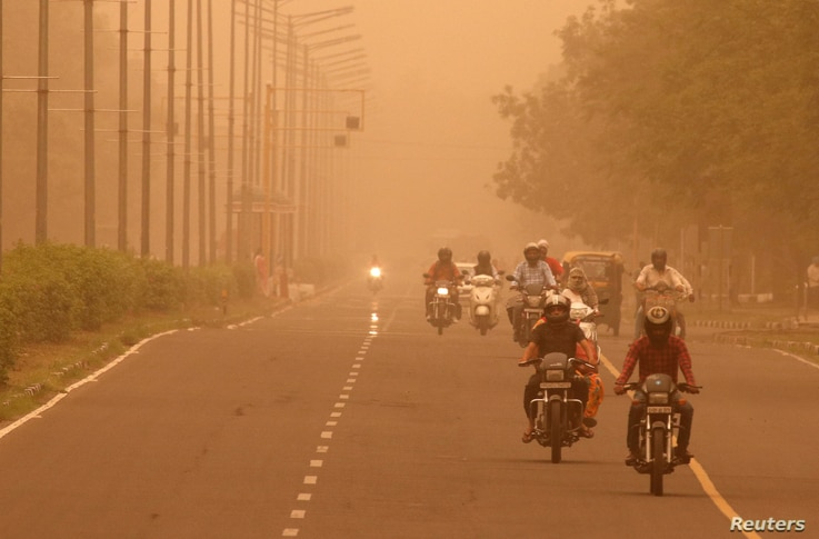 FILE - Commuters make their way amidst haze and dust in Chandigarh, India, June 15, 2018.