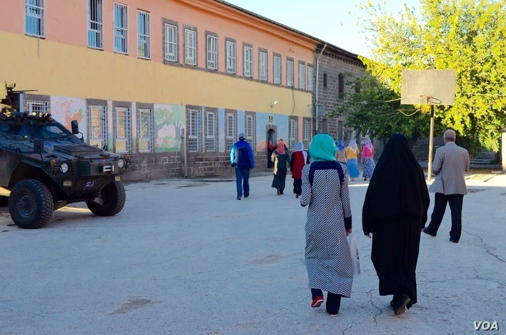 People approach a polling place in Diyarbakir Sunday morning while Turkish troops stand by. The government has warned of possible terrorist attacks to disrupt the election, but some people in this city have said they think the troop presence is unnec...