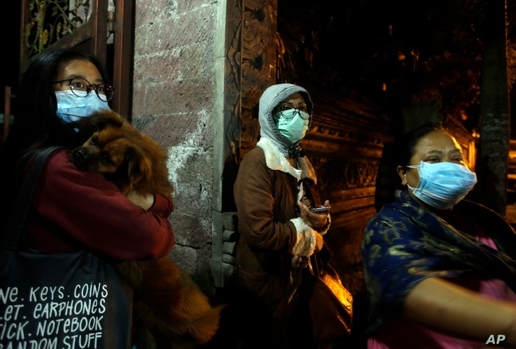Villagers wear masks as they prepare to evacuate from their homes near the crater of Mount Agung at Besakih village, Karangasem, Bali, Indonesia, Nov. 25, 2017. A volcano on the Indonesian tourist island erupted for the second time in a week on Satur