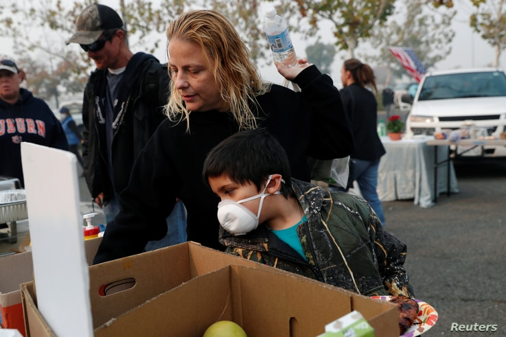 After losing their home in Magalia in the Camp Fire, Robin Tompkins and her son, Lukas, line up for a free meal in a makeshift evacuation center in Chico, Calif., Nov. 16, 2018.