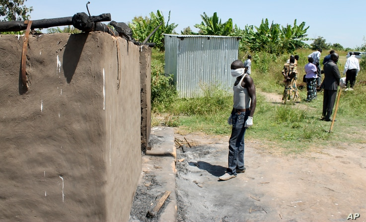 FILE - A man collecting bodies to bury in a mass grave approaches a burned hut containing charred corpses, on the outskirts of Yei, a center of the country's renewed civil war, southern South Sudan, Nov. 15, 2016.
