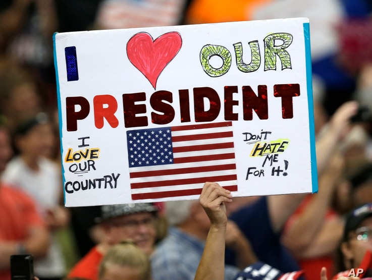 A supporter holds up a sign as President Donald Trump speaks at the Covelli Centre in Youngstown, Ohio, July 25, 2017.