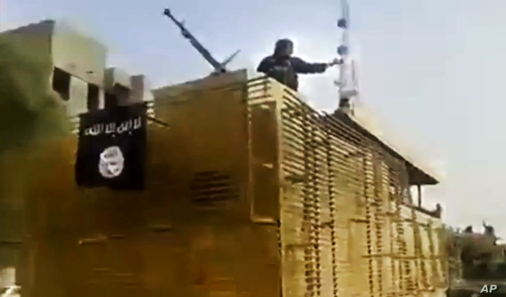 In this image taken from video uploaded to a militant social media account, which has been authenticated based on its contents and other AP reporting, al-Qaida-inspired Islamic State of Iraq and the Levant militants arrive to the country's largest ...