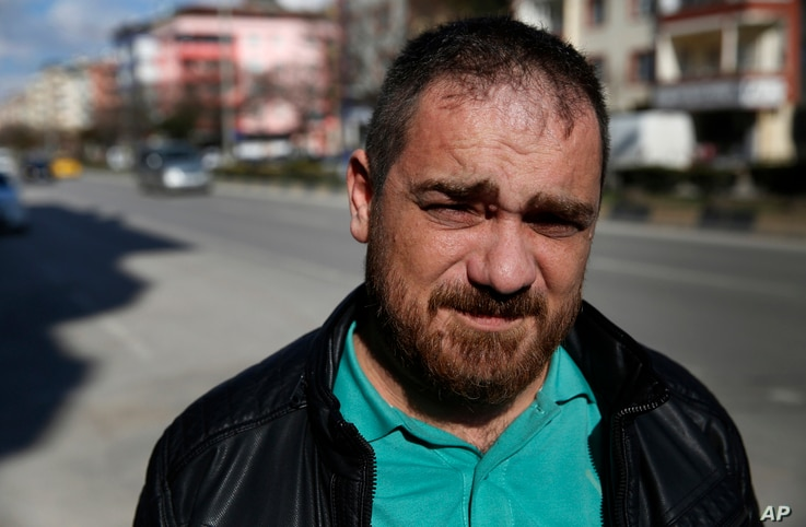 In this March 20, 2017, photo, Syrian Tarek Muharram, 39, who quit his banking job to return home and join the Syrian rebellion in 2012, poses for a photo in Gaziantep, southeastern Turkey, where he now lives.