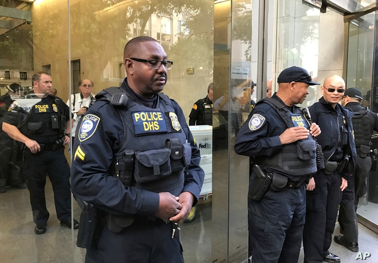 Officers from the Department of Homeland Security's Federal Protective Service stand guard as people demonstrate outside a federal immigration court in Los Angeles, March 6, 2017, protesting the arrest of an immigrant who has been ordered deported.
